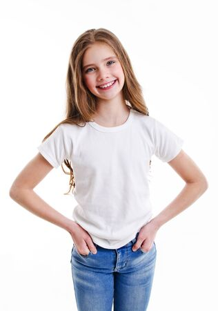 Portrait of adorable smiling little girl child preteen in jeans and white t-shirt isolated on a pink background Foto de archivo