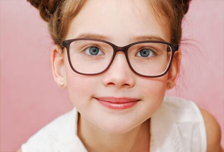 Cute little girl child preteen in eyeglasses education, school and vision concept isolated on a pink closeup Banco de Imagens