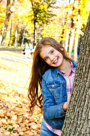 Autumn portrait of adorable smiling little girl child preteen standing near the tree in the park outdoors Stock Photo