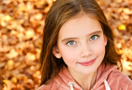 Autumn portrait of adorable smiling little girl child preteen in the park outdoors closeup Stock Photo