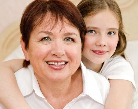 Cute little girl child and her grandmother are spending time together at home. Stock Photo