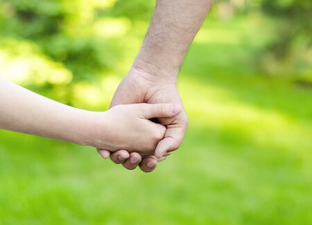 Child holding father hand outdoor. Care trust and helping concept Archivio Fotografico