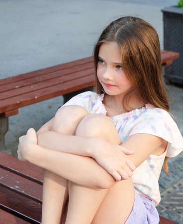 Portrait of sad upset little girl child in the summer day outdoors