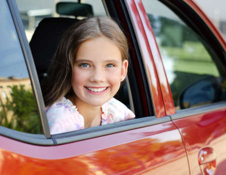 Happy cute little girl child looks out the window of the car in the summer day Banco de Imagens