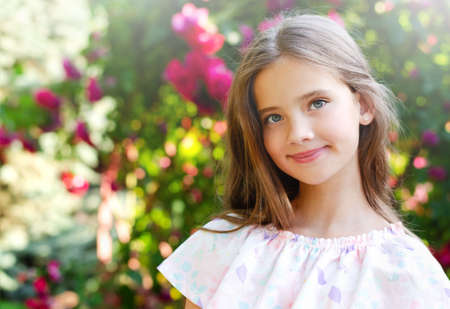 Portrait of adorable smiling little girl child in summer day. Happy preteen in the park outdoors Banco de Imagens