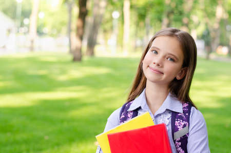 Back to school. Education concept. Cute smiling schoolgirl outdoor. Happy little girl child with backpack holding the books