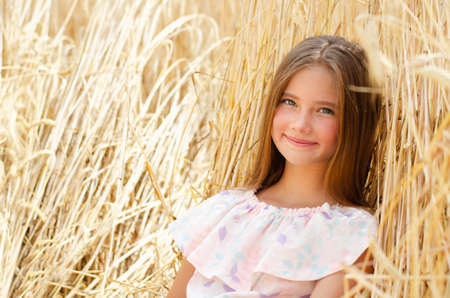 Portrait of smiling cute little girl child on field of wheat outdoor