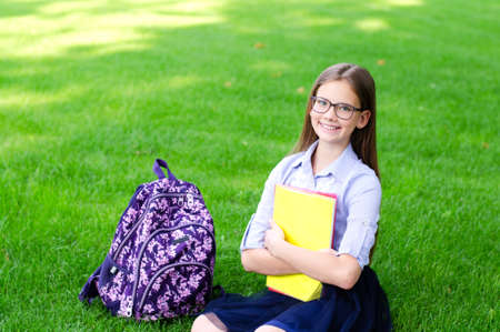 Back to school. Education concept. Cute smiling schoolgirl in glasses sitting on grass. Happy little girl child holding the books Zdjęcie Seryjne