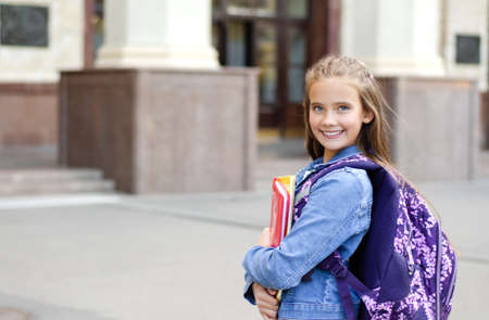Back to school. Education concept. Cute smiling schoolgirl preteen on the way to the school. Happy little girl child holding the books with backpack