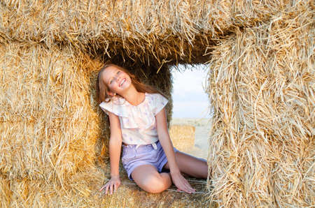 Adorable happy smiling ittle girl child sitting on a hay rolls in a wheat field at sunset Reklamní fotografie