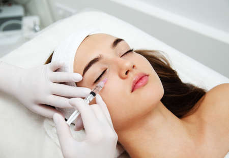 Woman getting cosmetic. injection. Beauty injections and cosmetology. Young woman in beauty salon sloseup. Plastic surgery and beauty treatment.