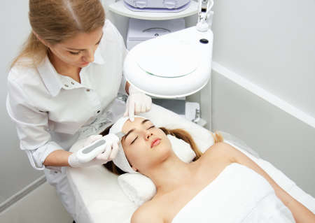 Woman getting facial beauty treatment in medical spa center. Skin care and rejuvenation concept. Beautician cleaning and touching female face. Attractive girl is lying and relaxing.