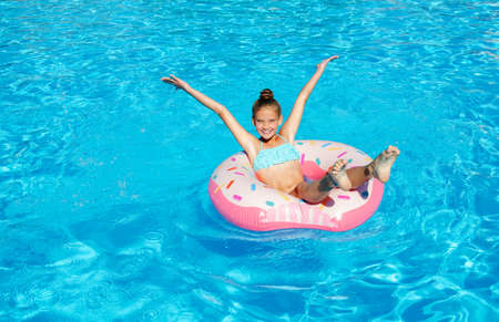 Cute smiling little girl in swimming pool with rubber ring. Child having fun on vacation in summertime