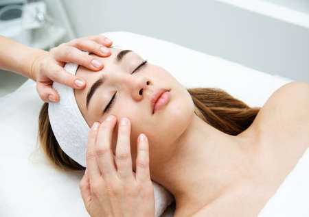Beautician massaging woman's face. Attractive girl having facial treatment and massage. The young woman is lying and relaxingin. Banque d'images