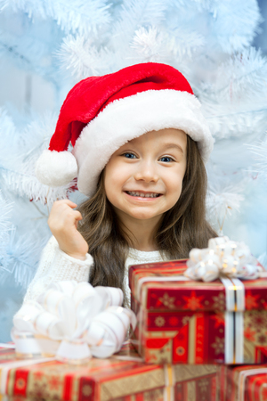 Child in Santa hat with gift box near white fir-tree photo