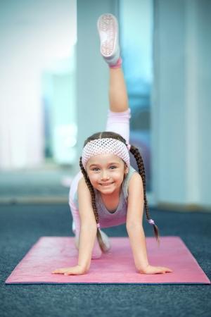 Kid doing fitness exercises near mirror photo