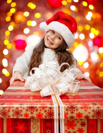 Child in Santa hat with big red gift box  photo