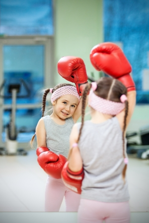Kid in boxing gloves near mirror photo