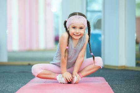 pied jeune fille: Kid faire des exercices de remise en forme pr�s de miroir Banque d'images
