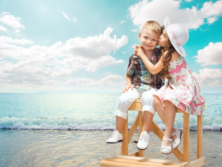 little girl smiling: girl embraces and kisses a boy