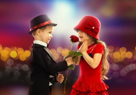 Krásný malý chlapec dává růži na módní dívka a její vzrušený Reklamní fotografie
