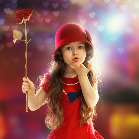 People, happiness concept  Happy little girl with rose in red clothes sends kiss her hand Standard-Bild