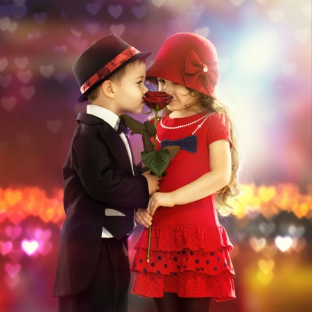 child s: Lovely little boy giving a rose to fashionable girl and her excited