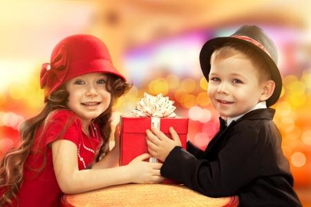 Malý chlapec dává dívka dárek dárek k narozeninám, Valentýn je den nebo svátek,