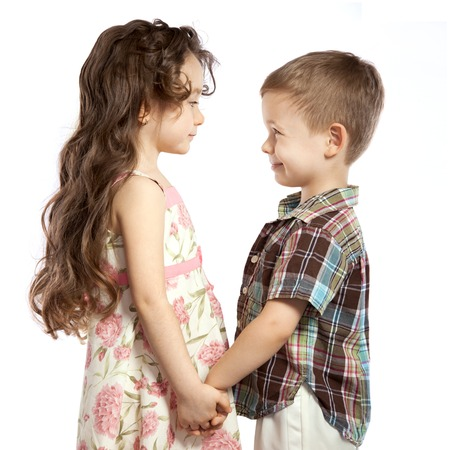Littlt girl looks at the boy and holding his hands photo