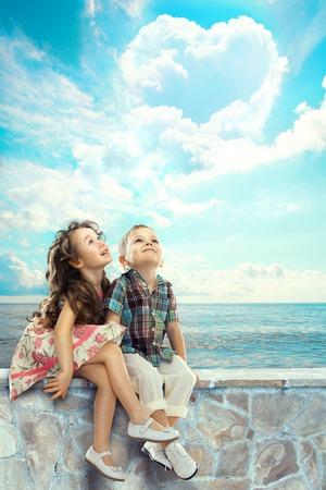 Šťastné děti při pohledu na modrou oblohu s mraky ve tvaru srdce lidí, štěstí koncept