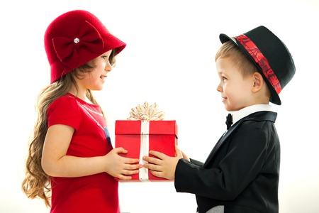gentleman s: Little boy giving girl gift  Present for a birthday, valentine s day, birthday or other holiday  Isolated on white background