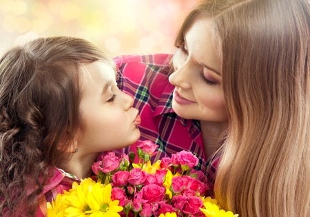 Daughter kissing happy mother with flowers  Mother s day concept  Family holiday