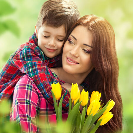 mother 's day: Son hugging happy mother with flowers  Mother s day concept  Family holiday
