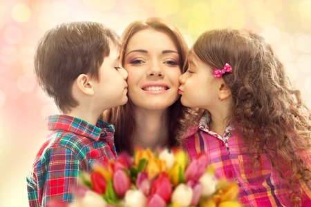 Portrait of children kissing her mother with flowers  Mother s day concept  Family holiday Standard-Bild