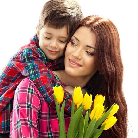 Syn objímání šťastná matka s květinami matek je den koncept Rodinná dovolená izolovaných na bílém pozadí