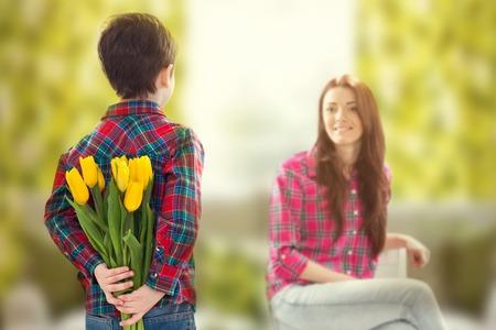 mamma e figlio: Vista posteriore lad con un mazzo di tulipani belli dietro la schiena prepara bella sorpresa per sua madre Madre s giorni di vacanza concetto di famiglia