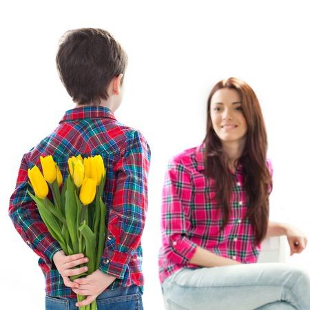 Zadní pohled kluk s partou krásných tulipánů za zády připravují milé překvapení pro svou matku Den matek koncept Rodinná dovolená izolovaných na bílém pozadí Reklamní fotografie