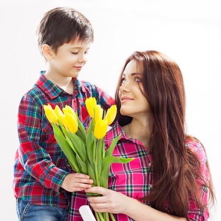 Syn objímá svou matku a dává jí květiny Spring, 8. března International Womens, Den matek, rodinná dovolená izolované bílé pozadí