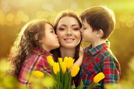 madre e hijos: Retrato de los niños besando a su madre con las flores de primavera, 8 de marzo de Internacional de la Mujer, Día de la Madre, día de fiesta de la familia