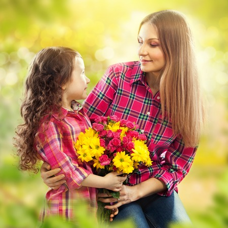 Daughter hugging his mother and gives her flowers  Spring, March 8, International Womens, Mothers day, family holiday photo