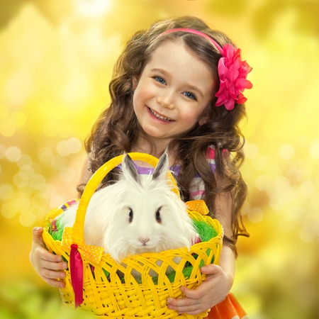 Happy little girl with easter rabbit in basket  Greeting card photo