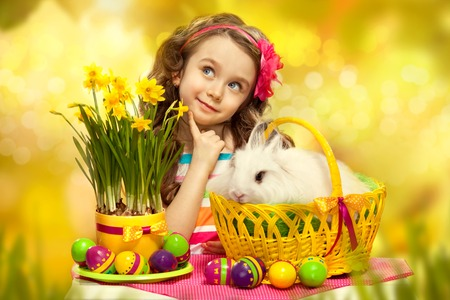 bunnie: Thoughtful little girl with easter rabbit in basket and eggs  Greeting card