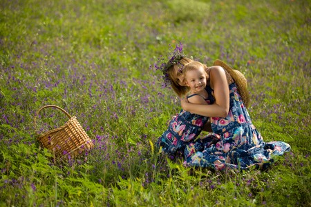 same: Happy mother playing with daughter in field  Outdoor shot Stock Photo