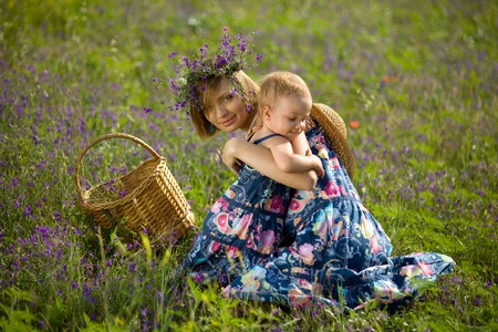 Happy mother playing with daughter in field  Outdoor shot photo