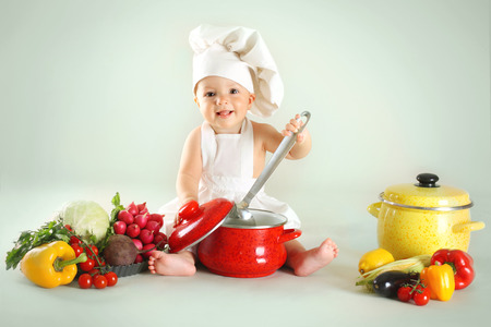 eating food: Baby wearing a chef hat with vegetables and pan  Use it for child, healthy food concept