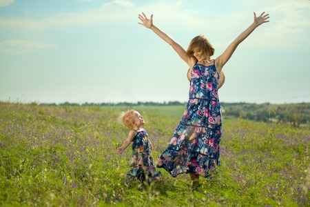 same: Happy mother and daughter standing in field  Outdoor shot