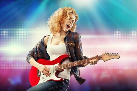 Portret van jonge mooie vrouw met gitaar spelen Geluk concept