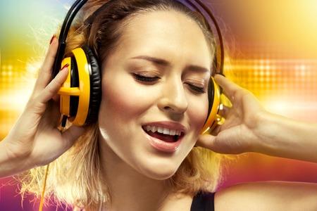 Mladá žena cítí šťastný poslechu hudby se sluchátky na uších štěstí koncepce