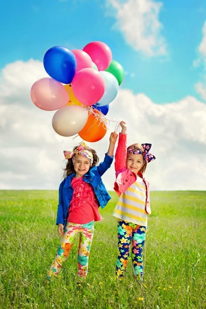 Cute happy children with balloons walking on spring field  Happiness, friendship, fashionable concept  Standard-Bild