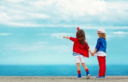 lejos: Moda niños se coloca en el rompeolas de piedra y recuerda a la de vacaciones de mar, la amistad, el concepto de moda Foto de archivo